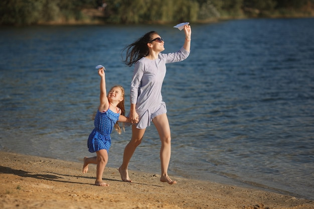Young mother and her cute daughter at the sea side launching paper aircrafts in the air and laughing