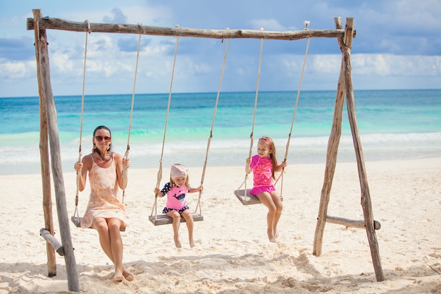 Young mother and her cute daughter swinging on a swing at the beach