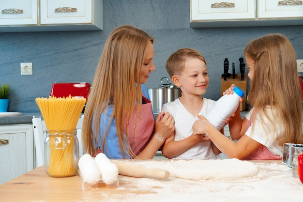 Young mother and her cute kids cooking pizza together