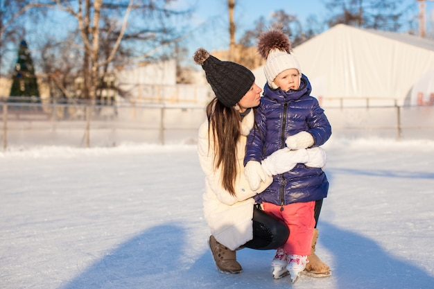 Young mother and her cute little daughter on a skating rink