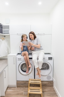 Young mother and her daughter are playing with tablet in laundry room sitting on washing machine