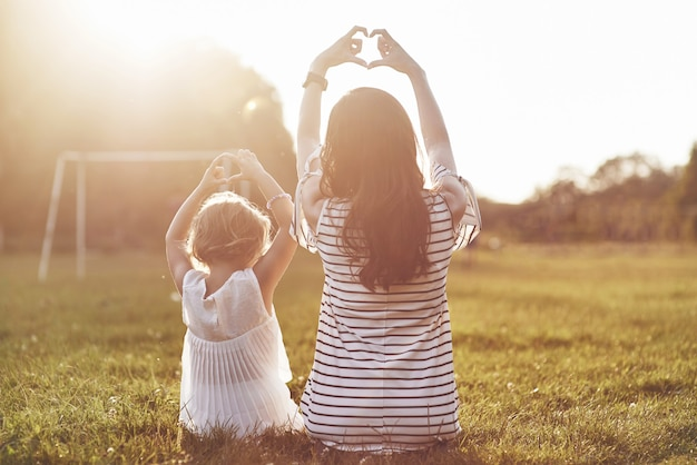 Young mother and her daughter sitting on the grass and making heart symbol to the sun