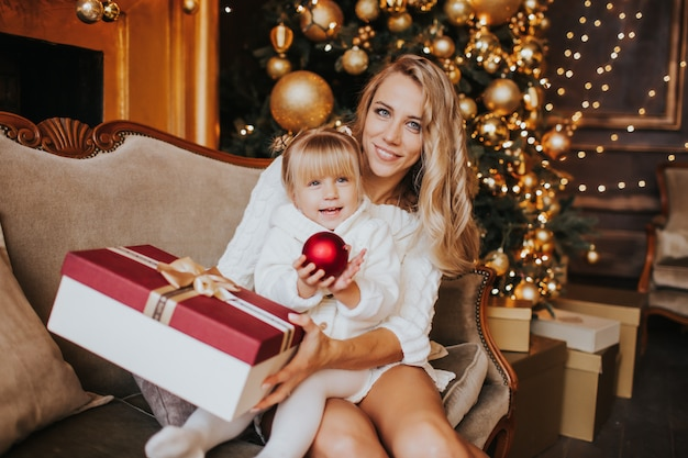 Young mother and her daughters in white knitted clothes opening a magical christmas gift by a christmas tree in cozy living room in winter