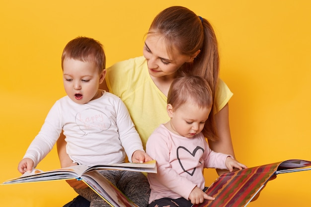 Young mother and her little babies daughters reading books, look on colorful pages, mommy keeps children in her knees while sitting on floor isolated over yellow