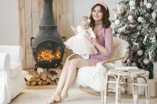 Young mother and her little baby daughter with christmas tree