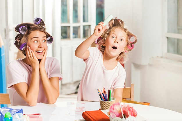The young mother and her little daughter drawing with pencils at home