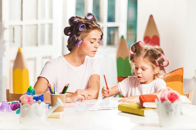 Giovane madre e la sua piccola figlia di disegno con le matite a casa
