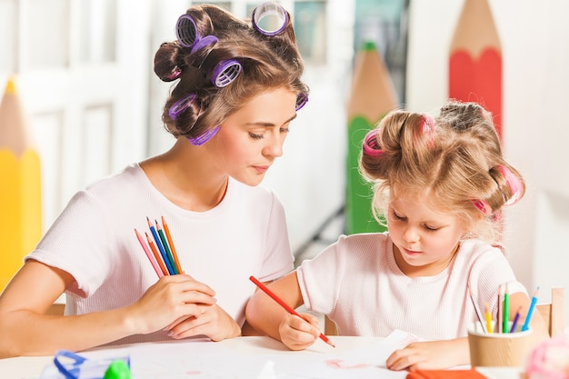 Young mother and her little daughter drawing with pencils at home