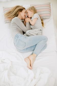 Giovane madre e la sua piccola figlia a casa al mattino pieno di sole. colori pastello tenui. tempo per la famiglia felice nel fine settimana. concetto di festa della mamma. concetti di famiglia, amore, stile di vita, maternità e momenti teneri.