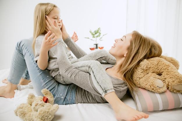 Giovane madre e la sua piccola figlia a casa al mattino pieno di sole. colori pastello tenui. tempo per la famiglia felice nel fine settimana. concetto di festa della mamma