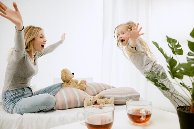 Giovane madre e la sua piccola figlia a casa al mattino pieno di sole. colori pastello tenui. tempo in famiglia felice nel fine settimana.