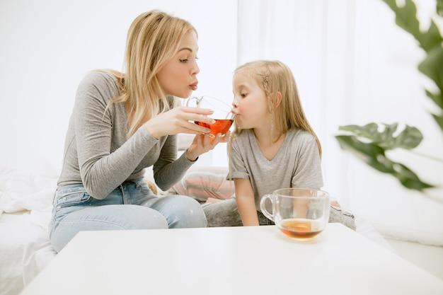 Giovane madre e la sua piccola figlia a casa al mattino pieno di sole