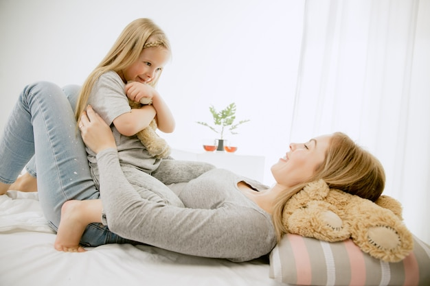 Giovane madre e la sua piccola figlia a casa al mattino pieno di sole.