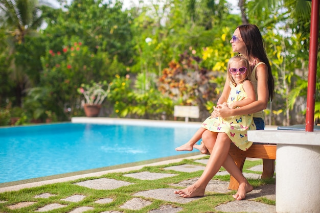 Young mother and her little daughter near the swimming pool