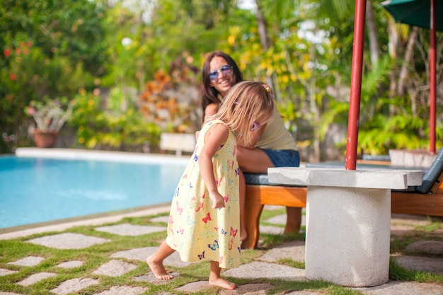 Young mother and her little daughter play near the swimming pool