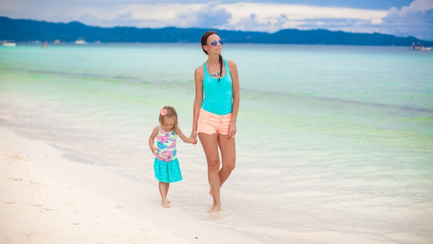 Young mother and her little daughter walking by the sea on philippines