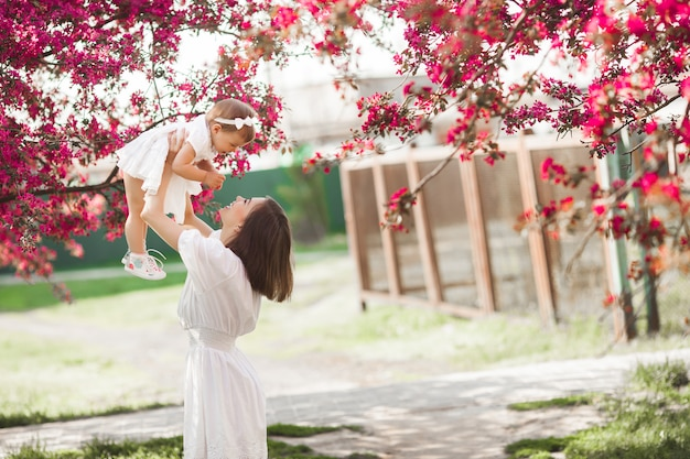 Young mother and her little daughter walking in the park together in the spring time. happy family outdoors. loving  with adorable baby girl.