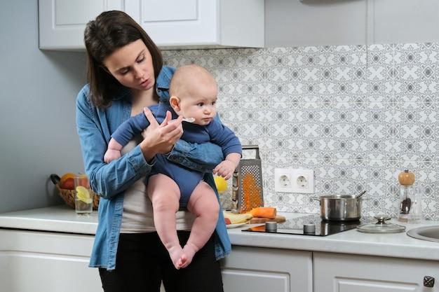 Молодая мать держит ребенка на руках, кормит его