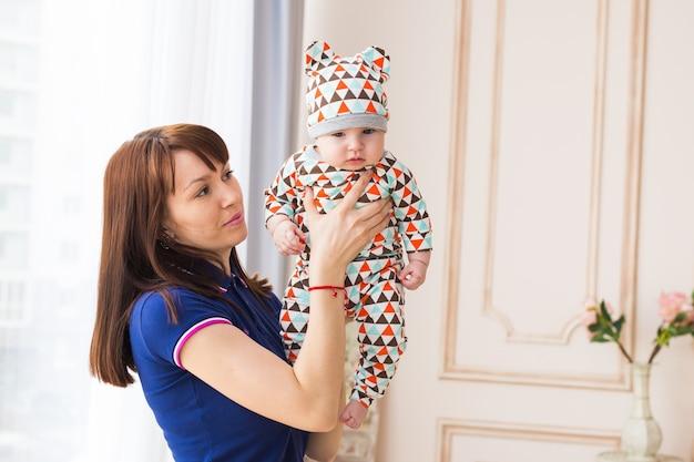 Молодая мать держит маленького сына в комнате.