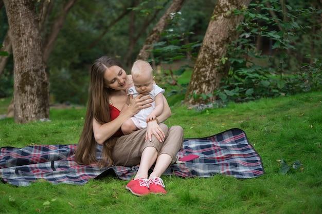 그녀의 팔에 그녀의 아기를 안고 피크닉 담요에 앉아 젊은 어머니. 행복한 모성.