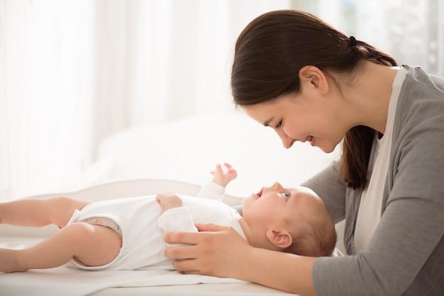 침실에서 그녀의 아기를 들고 젊은 어머니.
