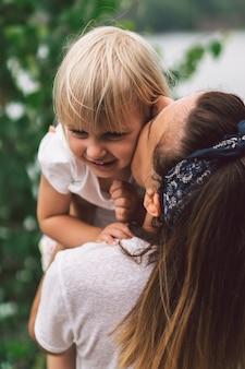 그녀의 아기를 들고 젊은 어머니. 어머니와 자연 속에서 좋은 시간을 보내고 작은 딸.
