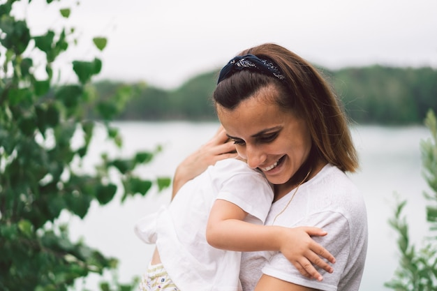Young mother holding her baby. mother and little daughter having good time in the nature.