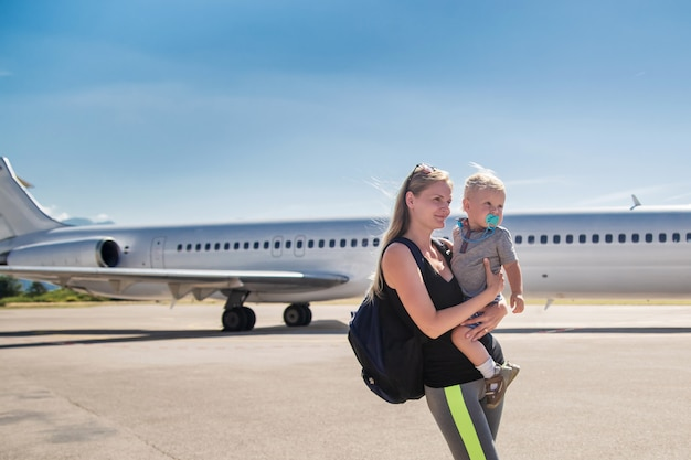 Young mother holding her baby son on the airplane and blue sky at the airport