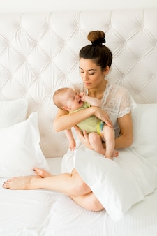Young mother holding her litle crying daughter on bed