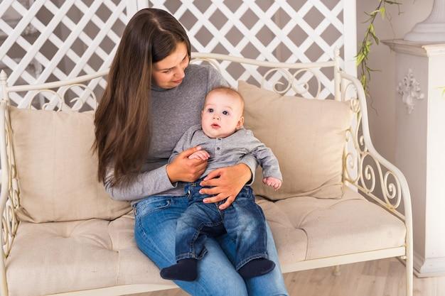 生まれたばかりの子供を抱く若い母親。女性と男の子は白い寝室でリラックスします。保育園のインテリア。家にいる家族。