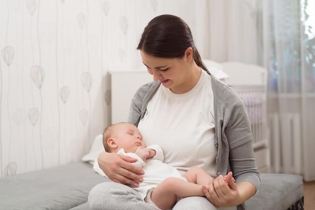 Молодая мать держит своего новорожденного ребенка.