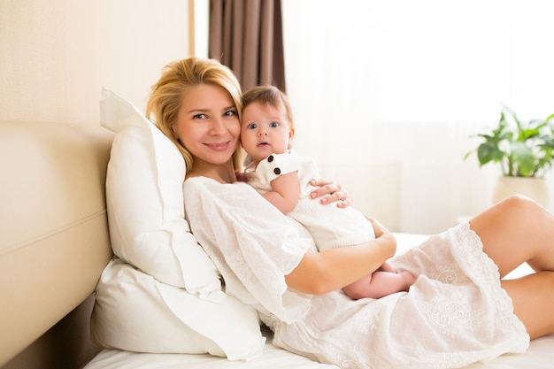 Молодая мать держит своего новорожденного ребенка. счастливая мама грудного ребенка. женщина и новорожденная девочка вместе в белой спальне дома. мать грудного вскармливания ребенка. семейный образ жизни