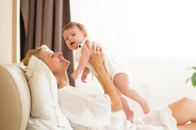 Young mother holding her newborn kid. happy mom nursing baby. woman and new born girl together in a white bedroom at home. mother breast feeding baby. family lifestyle
