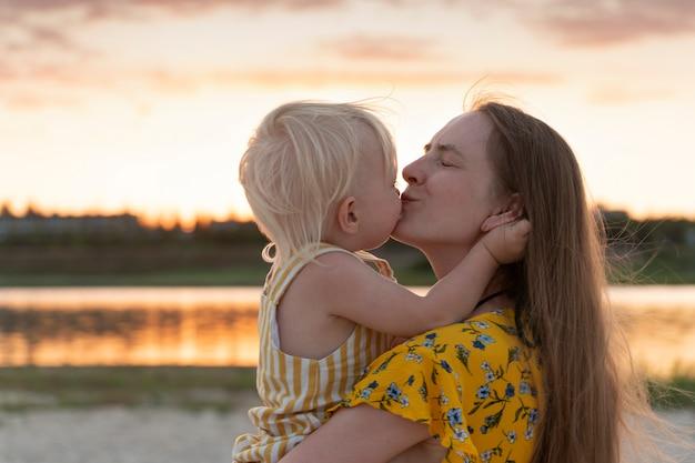 젊은 어머니는 작은 딸을 잡고 부드럽게 그녀를 키스합니다. 강 배경에 일몰에 초상화입니다.