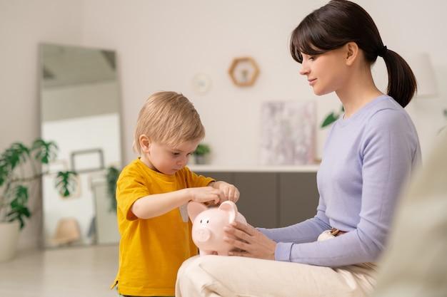 息子がそれにコインを入れている間貯金箱を持っている若い母親、お金を節約するために息子を教えている母親