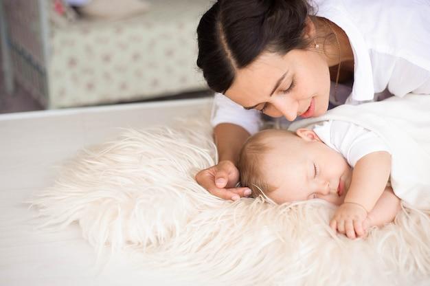 Молодая мать, нежно держа своего новорожденного мальчика