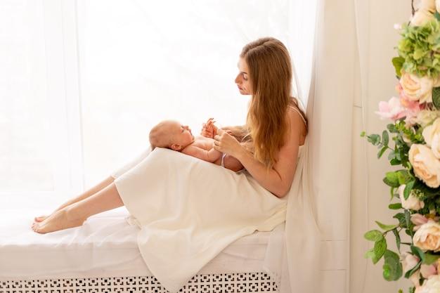 젊은 어머니는 그녀의 팔에 아이를 안고 창문에 앉아 존경합니다.