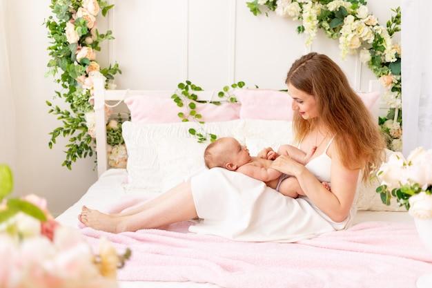 젊은 어머니는 그녀의 팔에 아이를 안고 아름다운 실내에서 다리에 키스