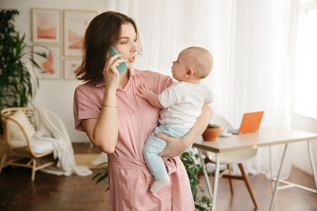 A young mother holds a baby in her arms and talks on the phone