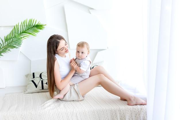 젊은 어머니는 침대에 아기 아들을 보유