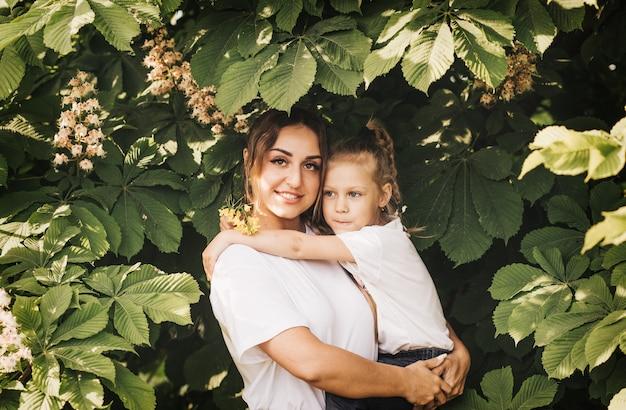 Молодая мать держит дочь летом. прекрасная семья и радость материнства.