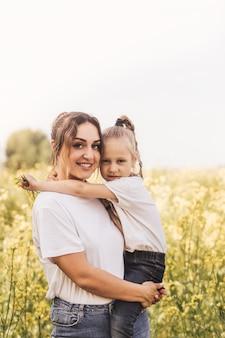 Молодая мать держит свою дочь летом на цветущем поле. прекрасная семья и радость материнства.