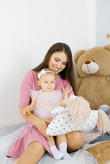 A young mother holds her little daughter in her arms in the children's room