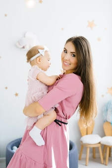 A young mother holds her little daughter in her arms. happy childhood and motherhood