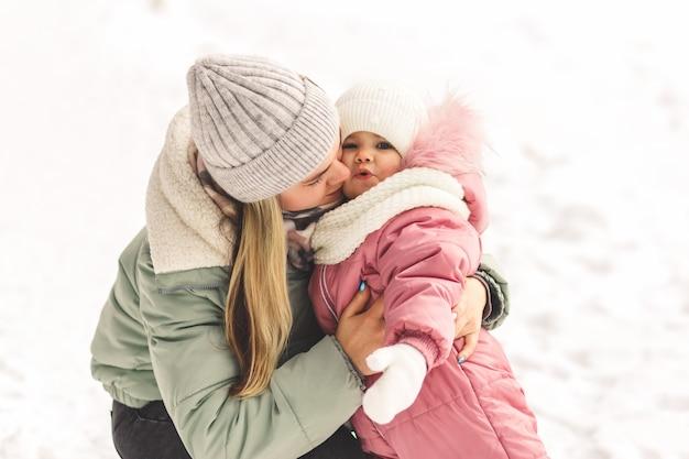 若い母親は幼い娘を抱きかかえてキスをします。家族写真。母性と子供時代