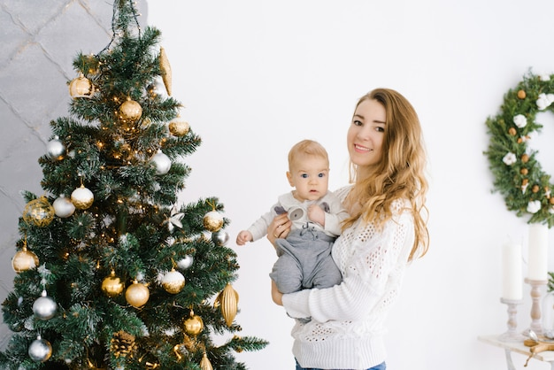 Young mother holds her young son in her arms near the christmas tree in the living room