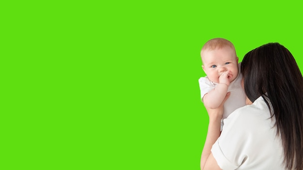 A young mother holds a smiling child in her arms on a green isolated background
