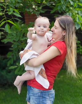 Young mother hugging her baby boy after swimming in outdoor swimming pool