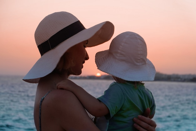 Young mother hugging her little daughter on a sunset