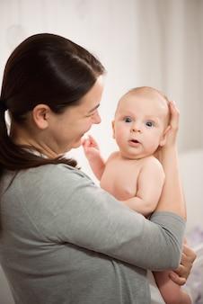 그녀의 신생아를 안고있는 젊은 어머니.